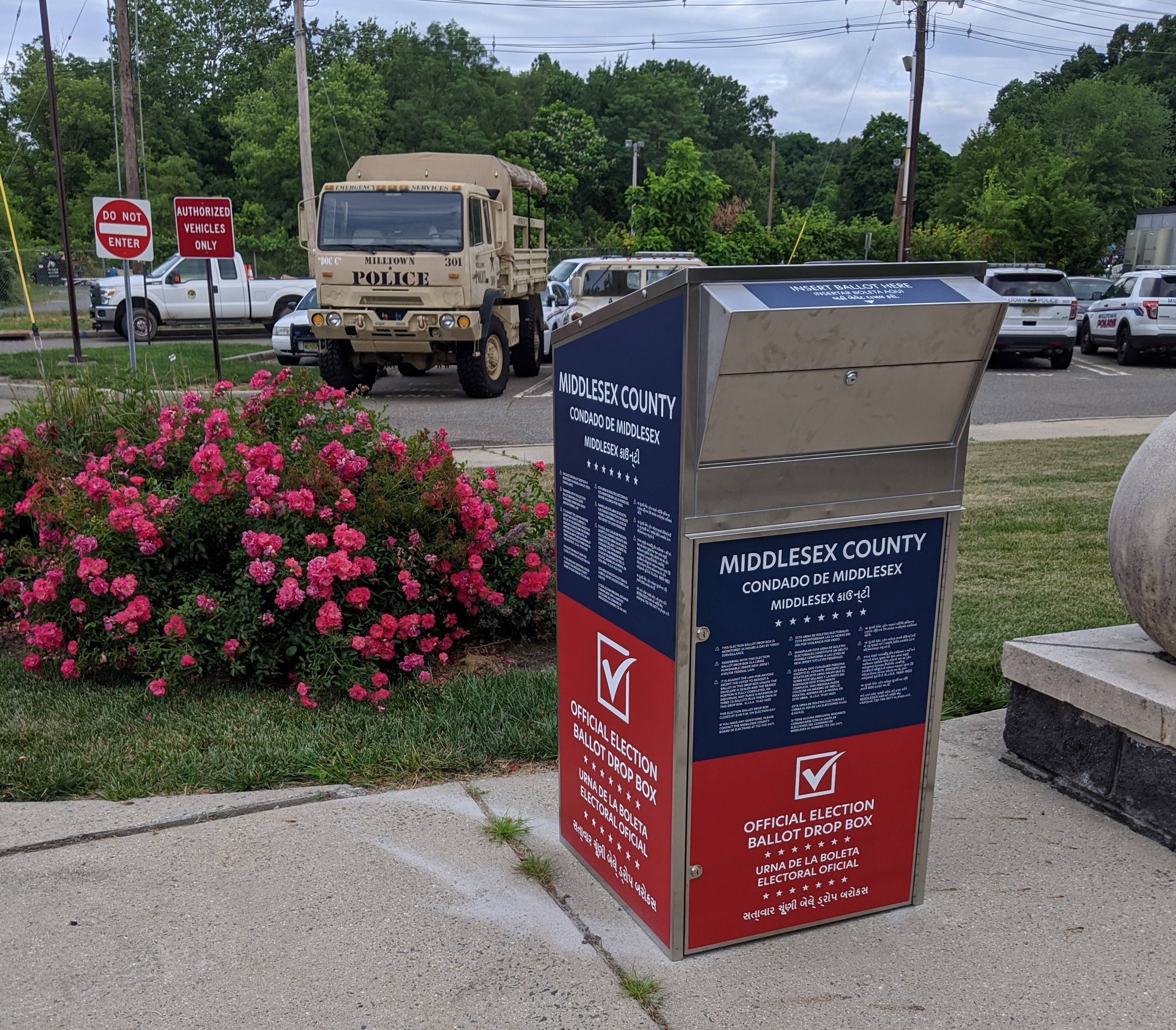 Image of the Vote By Mail Box near flower bush outside of Borough Hall
